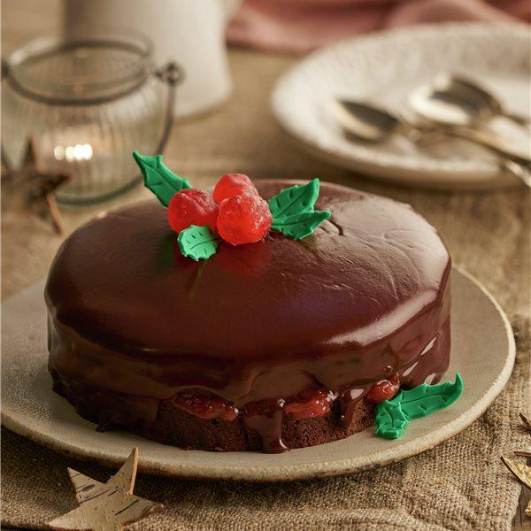 Bizcocho de chocolate con cerezas y hojas de acebo
