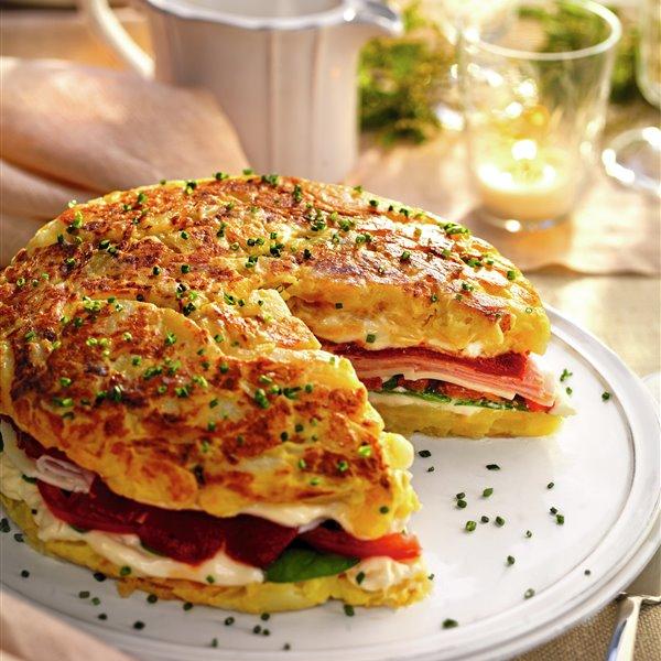 Tortilla de patatas rellena de tomate, pimiento, jamón y queso